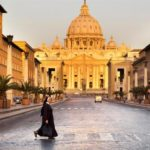 A nun looks both ways in front of St Peter's Basilica, in Rome